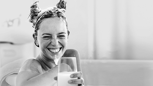 Woman bathes in a YUMA foam bath and drinks YUMA whey